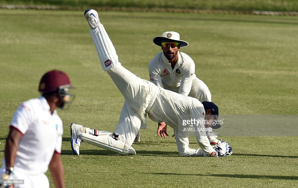 Indian wicketkeeper Wriddhiman Saha (C) dives to field the ball during Day 2 of the three-day tour match between India and WICB President's XI squad at the Warner Park stadium in Basseterre, Saint Kitts, on July 15, 2016. / AFP / Jewel SAMAD