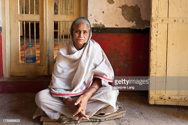 Indian widow dressed in white sari sitting on the floor of the Sri Bhagwan bhajan ashram in Vrindavan, Uttar Pradesh, India. Abandoned, stripped of...