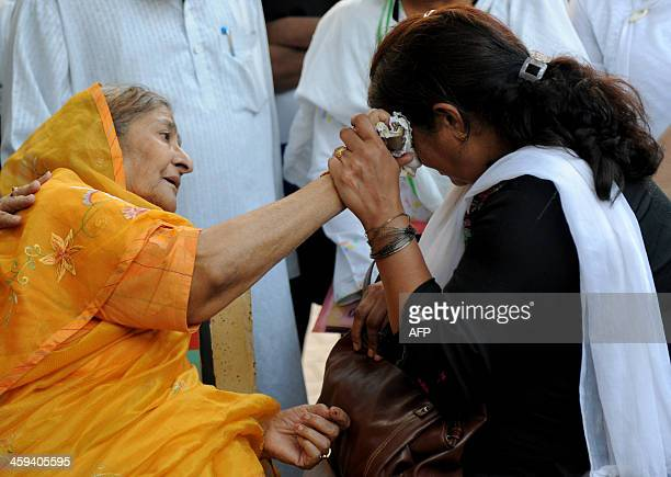 Indian widow Zakia Jafri comforts grieving mother Rupa Modi outside a court in Ahmedabad on December 26 following a judgement in favour of Chief...