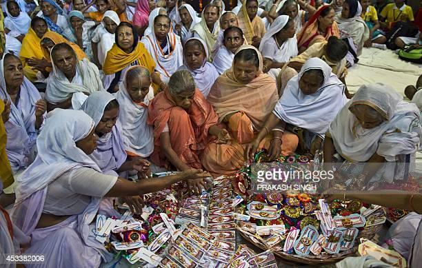 Indian widows chose 'rakhi' or sacred threads prior to celebrations for the Rakha Bandhan festival at the Meera Sahbhagini widows ashram in Vrindavan...