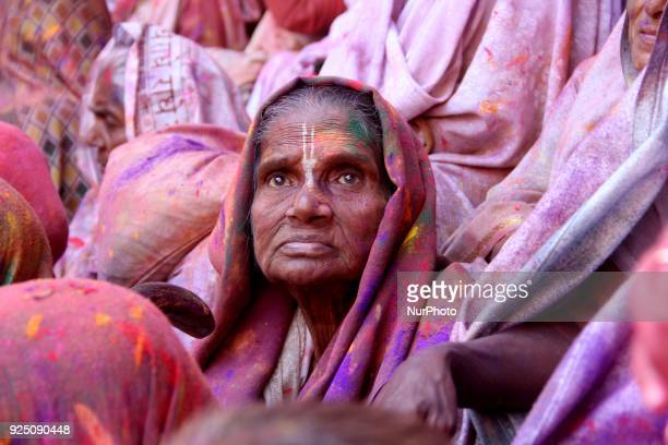 Indian widows covered in coloured powder sit aside while others dance during Holi festival or festival of colours celebrations in Vrindavan on...