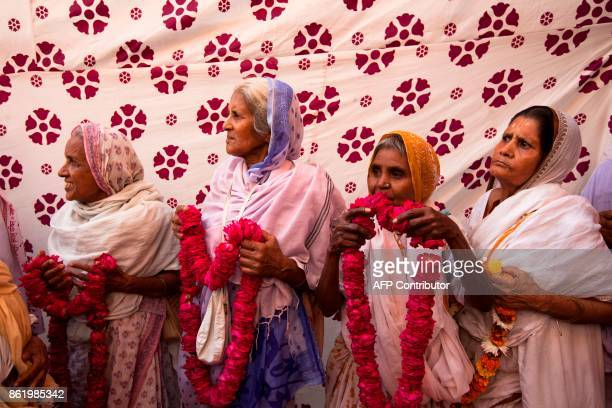 Indian widows hold garlands to welcome the groom at Gopinath temple in the Vrindavan on October 16 2017 India has the greatest number of widows in...