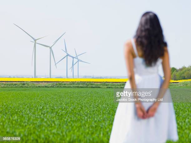 Indian woman admiring wind turbines in rural field