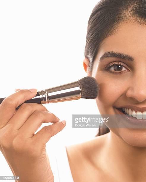 indian woman applying make up to face. - beautiful east indian women stockfoto's en -beelden