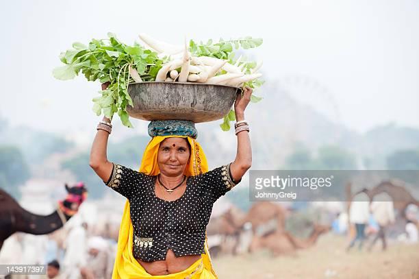 Indian woman carrying a big bowl of mooli
