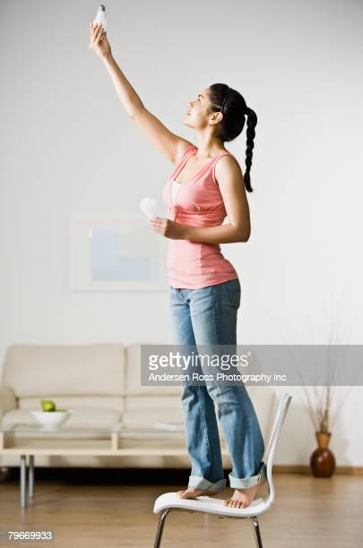 Indian woman changing light bulb