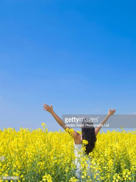 Indian woman cheering in field of flowers
