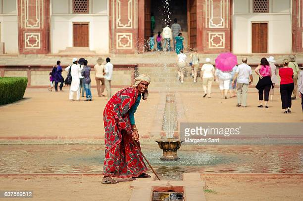 indian woman cleaning grounds at humayun's tomb, new delhi - sarri stock pictures, royalty-free photos & images