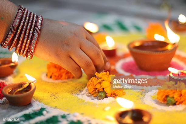Indian woman decorating Rangoli