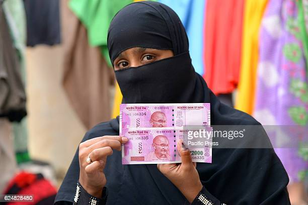 Indian woman display her inked finger and Rs 2000 bank notes Bank in India began inking the fingers of the people who exchange demonetized Rs 500 and...