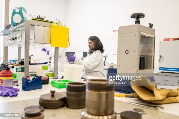 indian woman doing research in laboratory - physicist stock pictures, royalty-free photos & images