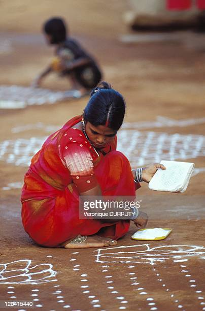 Indian woman drawing a kolam for a festival in Gokarna Karnataka India The art of kolam is a traditional and ancient India particularly in the states...