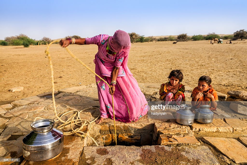 Indian woman drawing water from the well, desert, Rajasthan : Stock Photo