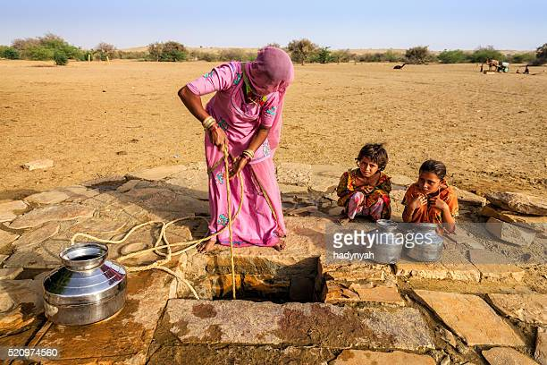 Indian woman drawing water from the well, desert, Rajasthan