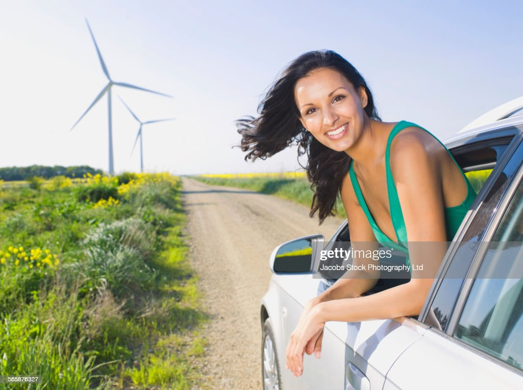 Indian woman driving in car near wind turbines : Stock Photo