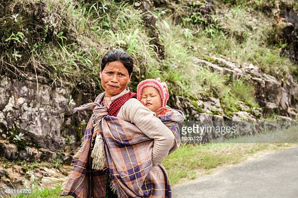 Indian woman from the Khasi tribe carrying baby down road.
