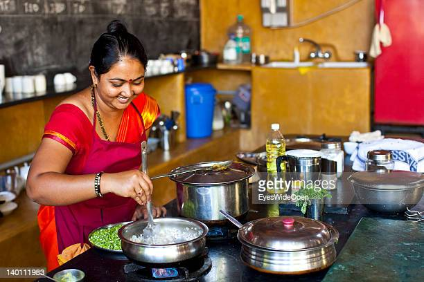 Indian woman Gita the chef prepares yellow lentil curry food in the kitchen of Yoga Magic Eco Retreat in Anjuna on February 1 2012 in Goa India
