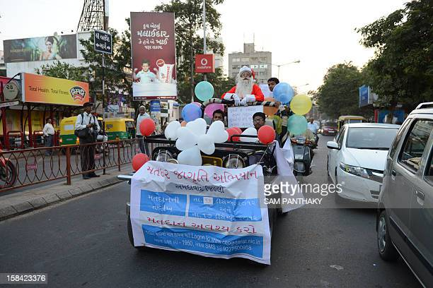 Indian woman Harshaben Prajapati dressed as Santa Claus rides a jeep while spreading awareness on voting in Ahmedabad on December 16 2012 The second...
