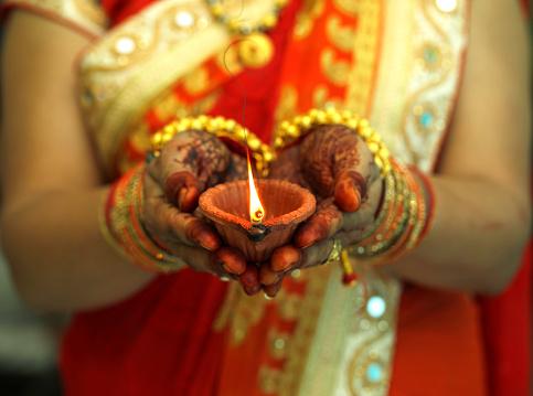 Indian woman holding Diwali oil lamp 864580928