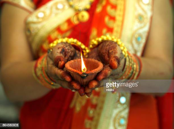 indian woman holding diwali oil lamp - diwali celebration stock photos and pictures