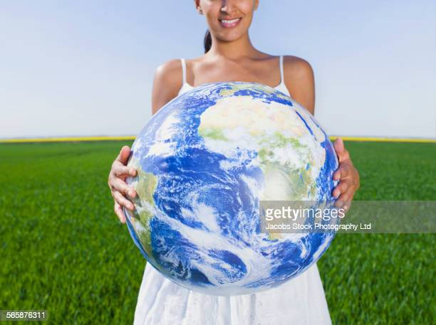 Indian woman holding globe in rural field