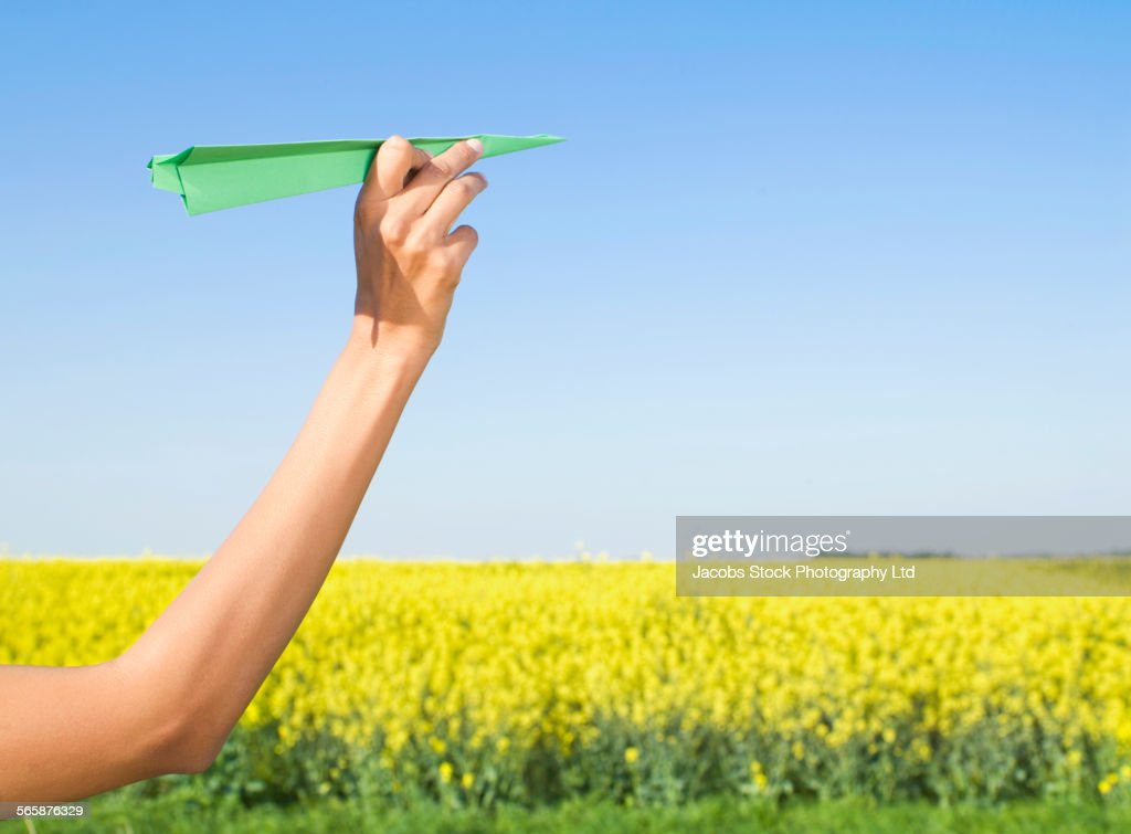 Indian woman holding green paper airplane in field of flowers : Stock Photo