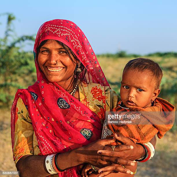 indian woman holding her baby - sari stock pictures, royalty-free photos & images
