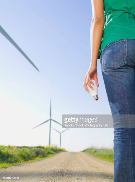 Indian woman holding light bulb near wind turbines