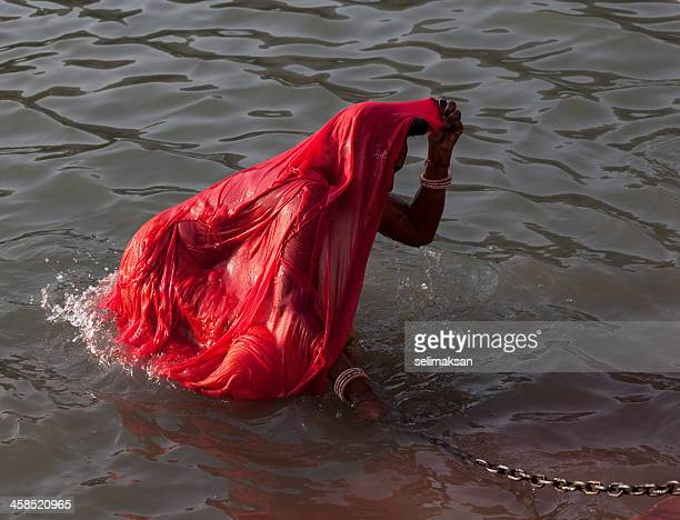 Indian woman holding security chain to get out of river