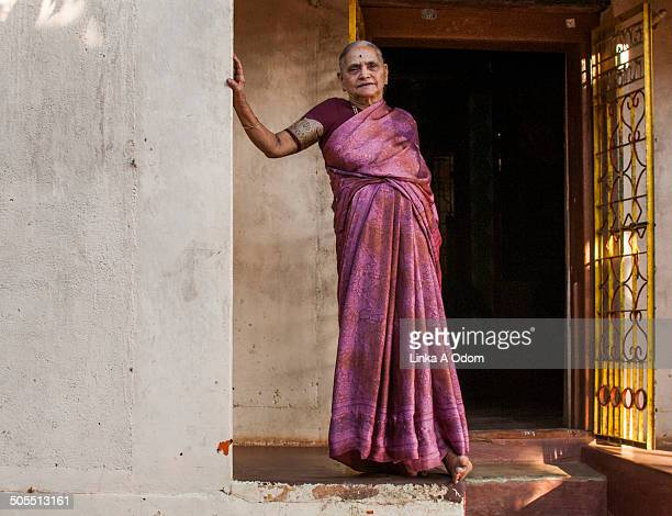 indian woman in pink sari standing on porch - sari stock pictures, royalty-free photos & images