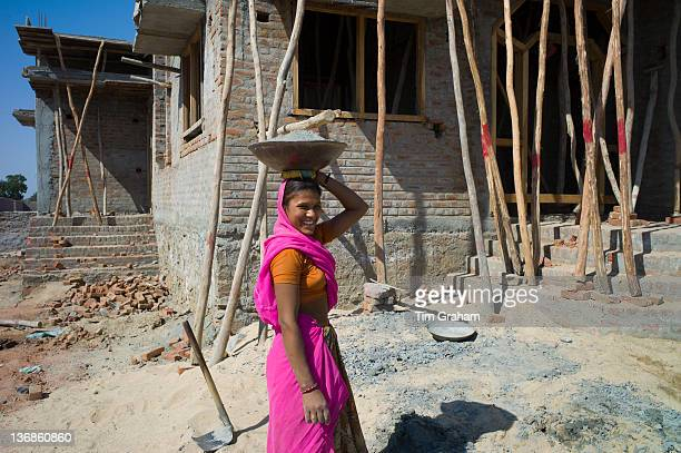 Indian woman in sari carrying cement while working on construction site at Khore village in Rajasthan Northern India