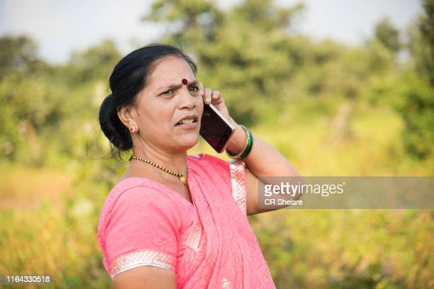 indian woman in traditional cloth using smartphone. - sari stock pictures, royalty-free photos & images