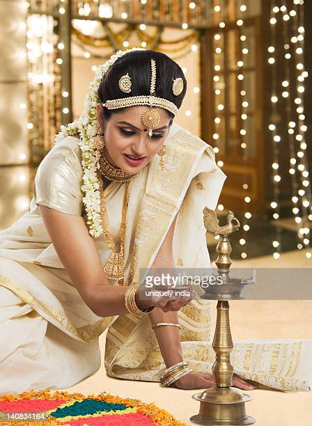 Indian woman in traditional clothing lighting an oil lamp