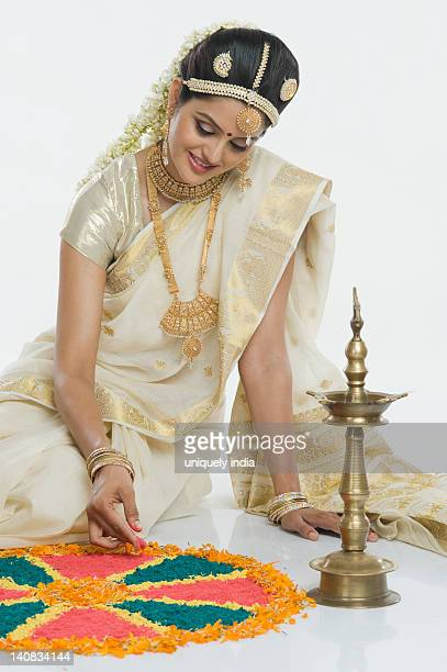 Indian woman in traditional clothing making rangoli at Durga festival