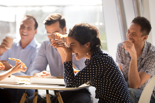 Indian woman laughing eating pizza with diverse coworkers in office 1070271762