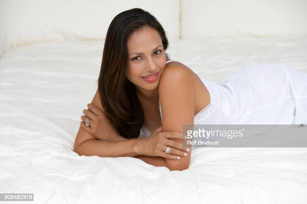 indian woman laying on bed - nachthemd stockfoto's en -beelden