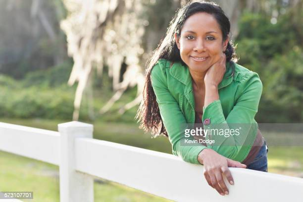 indian woman leaning on fence - hand on chin stock pictures, royalty-free photos & images