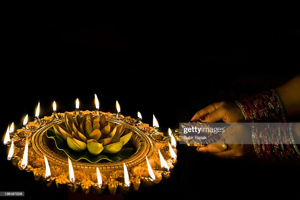 Indian Woman Lighting Oil Lamps During Diwali : Stock Photo