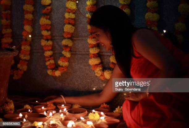 indian woman lighting oil lamps - diya oil lamp stock pictures, royalty-free photos & images
