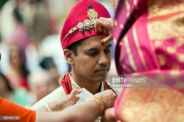 indian woman marking groom's forehead - bindi stock pictures, royalty-free photos & images