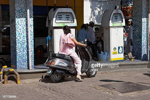 Indian woman on scooter at gas station