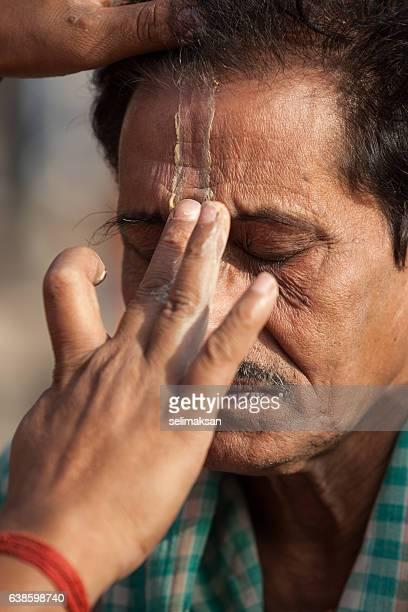 Indian Woman Painting Bindi On Man's Forehead