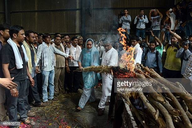 Indian woman Palakben Patel assisted by lawyer Babubhai Mangukiya lights the pyre of her brother Shwetank Patel at a cremetorium in the Babpunagar...