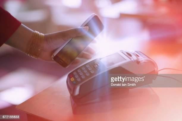 Indian woman paying with cell phone NFC technology