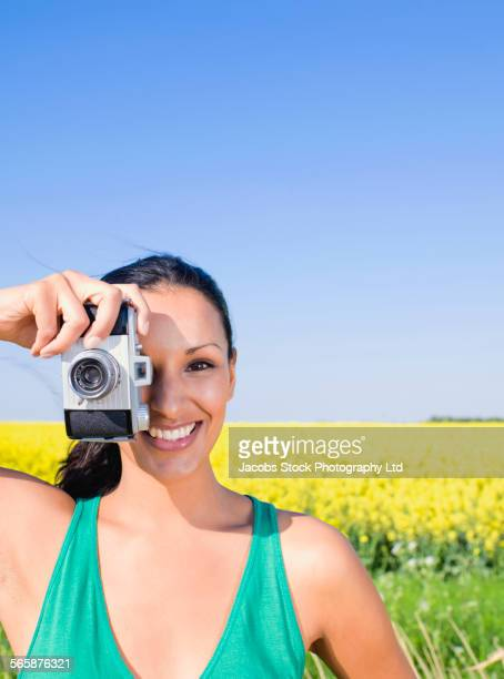 Indian woman photographing in field of flowers
