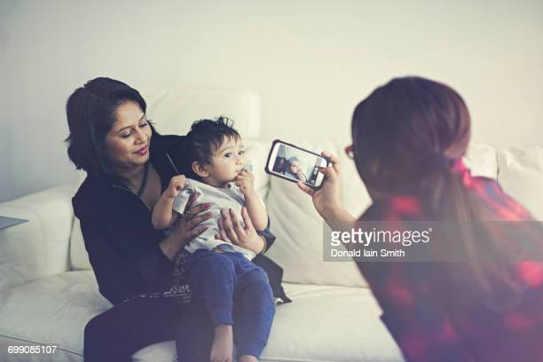 Indian woman photographing mother and son with cell phone