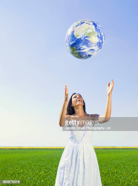 Indian woman playing with globe in rural field