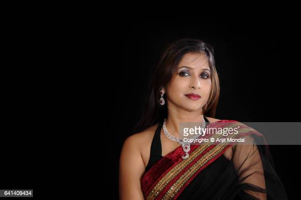 Indian woman portrait looking at camera in black sari black background copy space