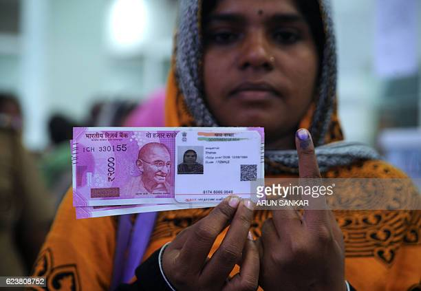 A Indian woman poses with new 2000 rupee notes her Aadhaar ID card and a finger inked with indelible ink after exchanging withdrawn 500 and 1000...