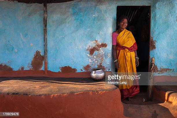 Indian woman posing at the doorstep of her traditional colorful house in Koraput village, south Orissa, India.